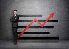 Full portrait of young businessman on a concrete background with increasing graph. Full portrait of a young businessman with his arms crossed isolated on a Stock Photography