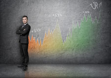 Full portrait young businessman with his arms crossed on background of an increasing graph Royalty Free Stock Image
