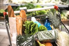 Full of products shopping trolley in supermarket. stock image
