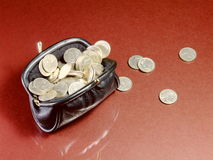 Full Purse. An old black leather purse, full to overflowing with small silver coins Stock Photos