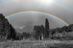 Full rainbow above black and white landscape in Colorado. Mountains Stock Photography