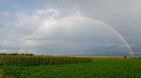 Full rainbow above farm fields with a cloudy sky. During summer time stock photography