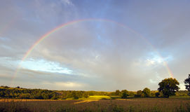 Full rainbow across landscape Stock Photos