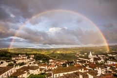 Full rainbow in the city of Obidos Portugal Stock Photos
