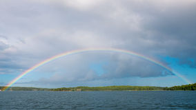 Full rainbow arc. A full rainbow arc over water and islands. Archipelago of Stockholm, Sweden Stock Images