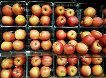 Full ram av röda äpplen som grupperas och staplas på skärmhyllor Arkivfoto