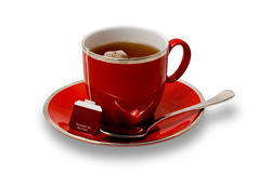 Full Red Teacup and Saucer with Teabag Isolated on Royalty Free Stock Photos