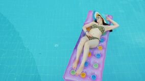 Full relaxation and no work and mobile phones, the girl is sunbathing on the mattress in the blue pool