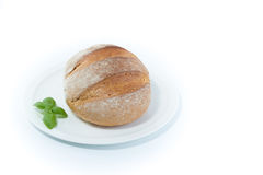 Full rustic loaf bread with basil leaves on a white dish isolate Royalty Free Stock Images