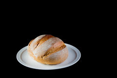 Full rustic loaf of bread on a white dish isolated on black back Stock Photography