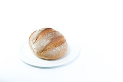 Full rustic loaf bread on a white dish isolated on white backgro Stock Image