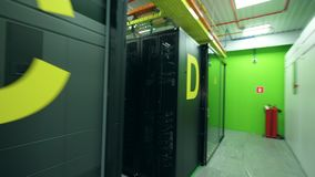 Full-scale server room with blocks of servers and office spaces. 4K stock footage