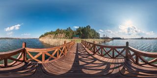 Full seamless hdri spherical panorama 360 degrees angle view on wooden pier of wide lake in sunny day. 360 panorama in royalty free stock image