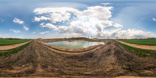 Full seamless panorama 360 angle view at the high cliff of the broad river bank in quarry for sand mining. Skybox as background in stock image