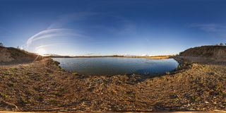 Full seamless panorama 360 angle view near quarry flooded with water for sand extraction mining in the evening sun in royalty free stock images