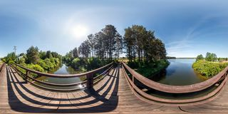 Full seamless panorama 360 by 180 angle view on wooden bridge across water canal against backdrop of huge lake in sunny summer day stock images