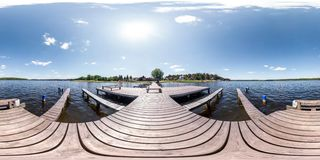Full seamless panorama 360 by 180 angle view wooden pier for ships on huge forest lake in sunny summer day in equirectangular royalty free stock image