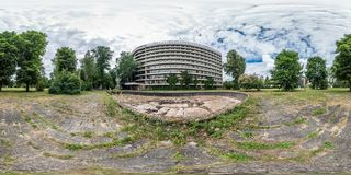 Full seamless panorama 360 by 180 degrees angle view facade of abandoned multi-storey, collapsing hotel near dry empty fountain stock images