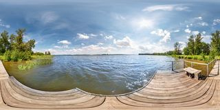 Full seamless spherical hdri panorama 360 degrees  angle view on wooden pier of huge lake or river in sunny summer day and windy. Weather with beautiful clouds stock images
