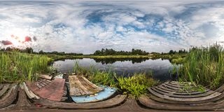 Full seamless spherical panorama 360 by 180 angle view on shore with garbage of small lake in sunny summer evening with awesome royalty free stock image
