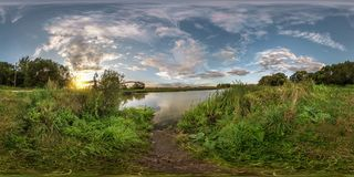 Full seamless spherical panorama 360 by 180 angle view on the shore of small lake in sunny summer evening with awesome clouds in. Equirectangular projection royalty free stock image