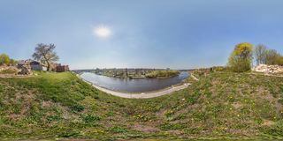 Full seamless spherical panorama 360 degrees angle view on bank of wide river in front of bridge near ancient destroed castle in stock photography