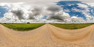 Full seamless spherical panorama 360 by 180 degrees angle view on gravel road among fields in sunny summer day with awesome clouds. In equirectangular stock photos