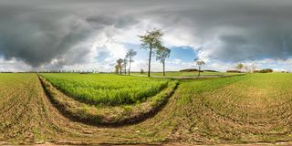 Full seamless spherical panorama 360 degrees angle view near asphault road among meadow fields in after storm with awesome clouds royalty free stock images