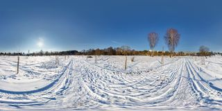 Full seamless spherical panorama 360 by 180 degrees angle view on the snow covered field in sunny winter day with halo in. Equirectangular projection, skybox VR royalty free stock images