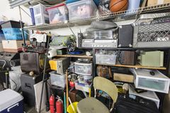 Full Shelves of Vintage Garage Junk. Full shelves of vintage electronics, boxes and sports equipment in typical suburban garage royalty free stock image