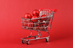 Full shopping basket of red matt and glossy christmas balls on red background Stock Images