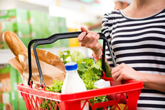 Full shopping basket. Woman shopping at store with shopping basket Stock Photography