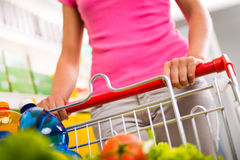 Full shopping cart at supermarket. Full shopping cart at store with fresh vegetables and hands close-up Royalty Free Stock Photos
