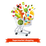 Full shopping grocery cart exploding with goods Royalty Free Stock Images