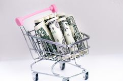 Full shopping trolley with dollar banknotes on a white background. Isolated. Concept of consumerism and money. Full shopping trolley with dollar banknotes on a Royalty Free Stock Photography