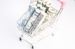 Full shoppingspårvagn med dollarsedlar på en vit bakgrund isolerat Begrepp av consumerism och pengar Arkivbild