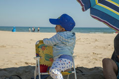 Full shot baby boy standing in a plastic chair at the beach. Stock Photos