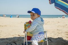 Full shot baby boy standing in a plastic chair at the beach. Royalty Free Stock Photo