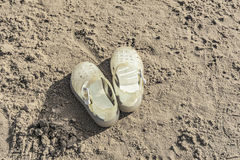 Full shot baby sandals on sand beach Royalty Free Stock Images