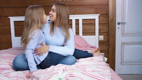 Barefoot baby girl talking smiling and hugging with young pretty woman sitting on bed in bedroom stock video
