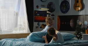 Boy and girl playing pillow fight on bed. Full shot of a boy and a girl playing pillow fight on a bed stock photography