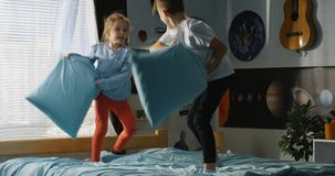 Boy and girl playing pillow fight on bed. Full shot of a boy and a girl playing pillow fight on a bed stock photos