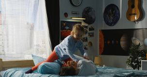 Boy and girl playing pillow fight on bed. Full shot of a boy and a girl playing pillow fight on a bed royalty free stock image