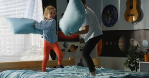 Boy and girl playing pillow fight on bed. Full shot of a boy and a girl playing pillow fight on a bed royalty free stock photo