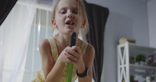 Girl singing with mop handle stock video footage