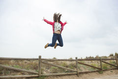 Full shot happy teenager jumping with outstretched hands near th Stock Photos