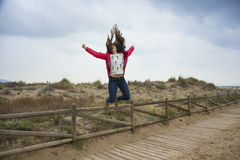 Full shot happy teenager jumping with outstretched hands near th Stock Photo
