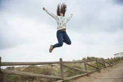 Full shot happy teenager jumping with outstretched hands near th Stock Photography