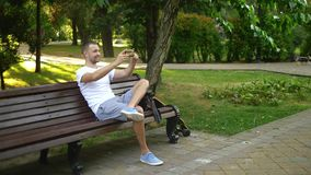 Full shot. A man blogger uses a smartphone while sitting on a park bench. He has a video call with someone stock video footage