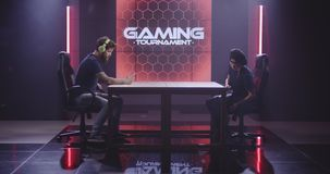 Man and woman competing at a mobile gaming tournament. Full shot of a man and woman sitting down at a table to compete at a mobile gaming tournament stock footage